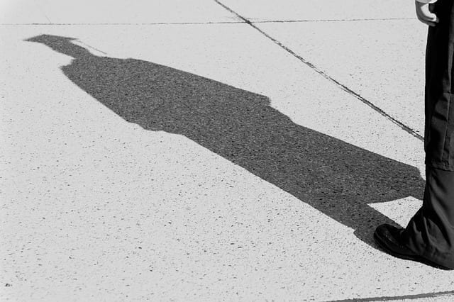 A graduate standing in the sun with a long shadow